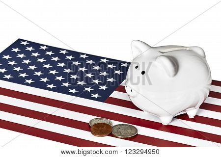 White ceramic piggy bank with two quarters and a penny on top of an American flag isolated on white