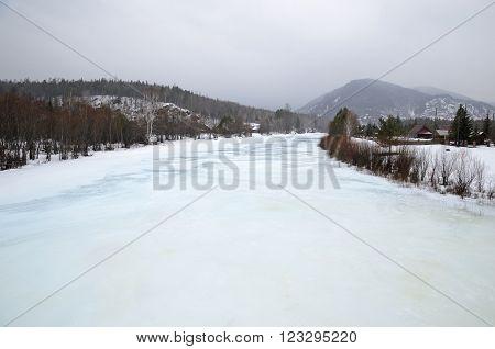Icebound river on a cloudy spring day in the village. Kochergat Irkutsk Region Russia