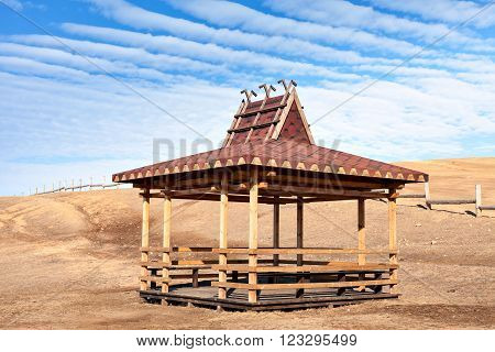 Traditional wooden gazebo in the Buryat-style on the shore of Lake Baikal in the winter. Winter Landscape on Olkhon island. Buryat region, Russia, Siberia.