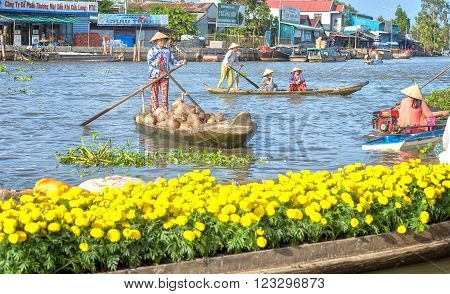 Soc Trang, Vietnam - February 2nd, 2016: Women farmers are selling coconut boating on the river's busiest air boats back and forth, the front is bright yellow daisies boatload make real river scene in the country beauty in Soc Trang, Vietnam