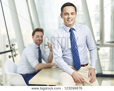 successful caucasian business leader sitting on desk in office smiling with colleague in background.