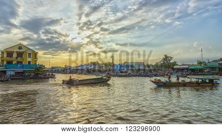 Soc Trang, Vietnam - February 2nd, 2016: Afternoon on the river with many boats homeland on the river back and forth as the sun rays radiating end of the day makes the scene more idyllic countryside and the rustic countryside in Soc Trang, Vietnam