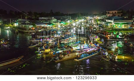 Soc Trang, Vietnam - February 3rd, 2016: Landscape purchases Floating Market at night with bustling boats crossing river in roundabout sales agricultural products  prepare to welcome Lunar New Year in Soc Trang, Vietnam