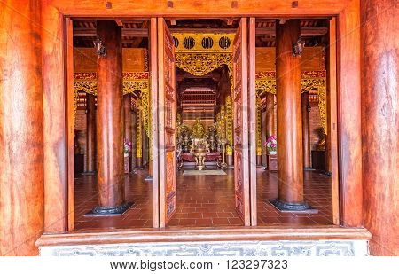 Can Tho, Vietnam - February 4th, 2016: The beauty architecture monastery gate with the door structure classified forest, the large wooden poles, roof tiles, floor tiles Bat Trang are all red create a cool atmosphere, bar net to develop the mind in Can Tho