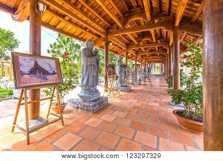 Can Tho, Vietnam - February 4th, 2016: Beauty architecture Monastery hallway with large wooden poles, roof tiles, statues, Buddha paintings arranged harmony create cool atmosphere in Can Tho, Vietnam