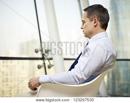 caucasian business executive sitting by the window in a chair thinking in office.