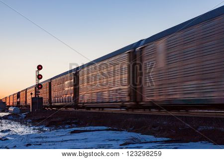 A line of railway cars speeding past at sunset with a red signal tower visible in the snow