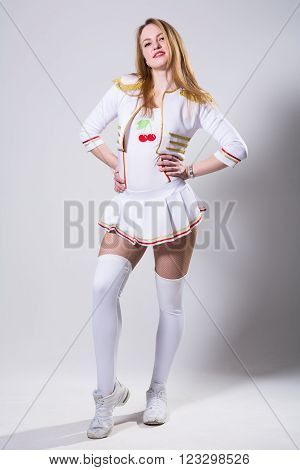 Cheerleader isolated on the white background. Young modern dancer in a pose full length in the studio