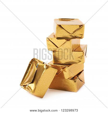 Stack of mulitple bouillon stock broth cubes wrapped in golden foil, composition isolated over the white background