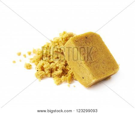 Crushed yellow bouillon stock broth cube isolated over the white background