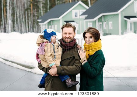 happy family against a country house and real estate