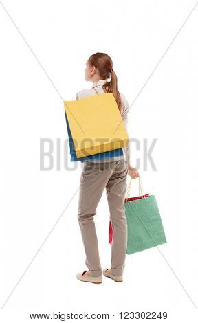 back view of woman with shopping bags . beautiful brunette girl in motion.  backside view of person.  Isolated over white background. Girl in light trousers standing with a variety of paper bags.