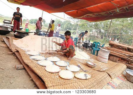Shariatpur District, Bangladesh - February 14, 2016:  Cooked rice heap  and serving at traditional village feast for almost 6000 people from all levels of society.