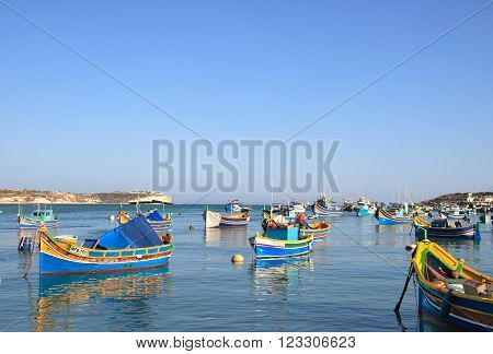 MARSAXLOKK, MALTA - JUNE 9, 2007: Colourful fishing boats in the Mediterranean on June 9, 2007 in Marsaxlokk, Malta.  Marsaxlokk is a famous traditional fishing village in Malta.