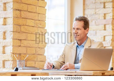 Follow your tasks. Positive pleasant upbeat man making notes and looking aside while working at the table