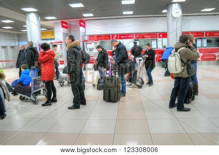 SHEREMETYEVO, RUSSIA - March 18, 2016: Passengers wait a train near the cashdesks of aeroexpress in an airport.