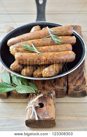 Thin fried sausages in a pan on a wooden background