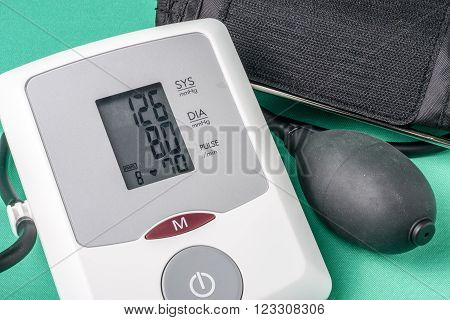 automatic blood pressure monitor on a green background.