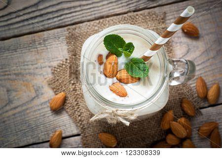 Shake from almond milk banana and coconut in a mason mug. Dairy free.