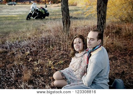 Man and woman in the forest autumn. Enamored couple sitting side by side on grass and looking to side. In background, a motorcycle and a car