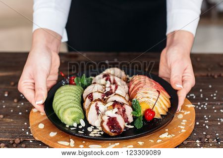 Waiter serving a baked veal with fresh fruits and sweet  sauce . Waiter serving baked veal for retail. Chief decorating food for presentation in restaurant.