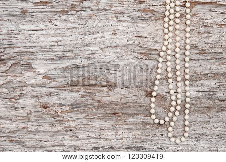 Vintage Background With Bead Necklace On The Old Wood