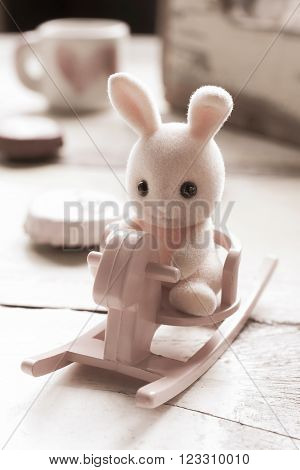 Pink toy rabbit sitting on rocking horse .Processed with vintage style. Shallow depth of field.