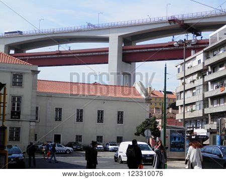LISBON, PORTUGAL - MARCH 17TH. The Bridge of April 25th running high over Lisbon rooftops. Lisbon Portugal March 17th 2016