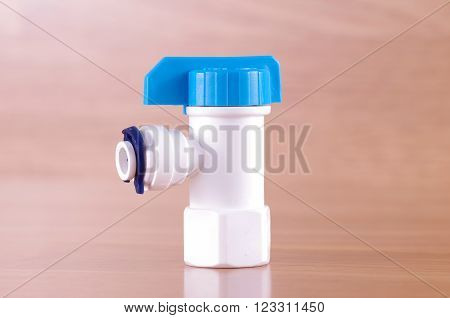 Plastic tap on wooden background. Plastic tap from Reverse Osmosis water filter system.