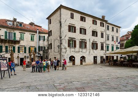 KOTOR MONTENEGRO - SEPTEMBER 21 2015: Unidentified tourists are near the Archive building on St. Tryphon Square Old Town Kotor Montenegro