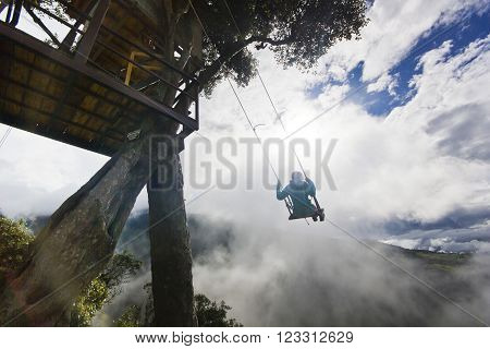 girl in swing in ecuador mountains near volcan with breakage with cloudy weather