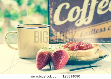 Coffee with milk and toast with strawberry jam ** Note: Shallow depth of field