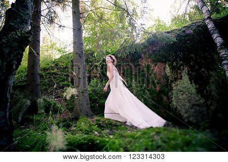 a young girl in a white dress and a blindfold in a forest at the rock in moss