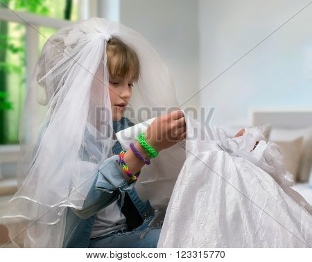 Teen girl trying on wedding dress and veil. The concept of early marriage, dreams of a wedding.