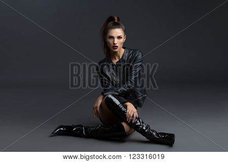 Beautiful young woman with dark makeup in leather jacket and boots over grey background. Copy space.