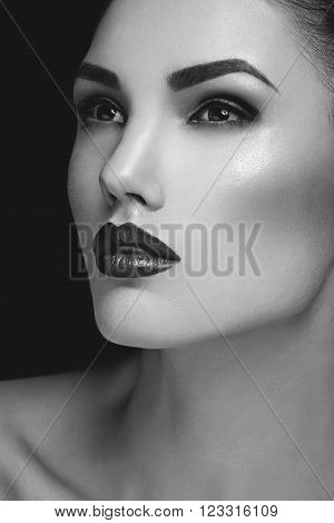 Beautiful young woman with dark red lips and eyeshadows. Beauty shot. Over grey background. Copy space.