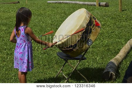 Caribou, Maine/USA August 23 2015: Native American Micmac tribe girl pounds a handmade drum at an annual Pow Wow in the Northern Maine town of Caribou on August 23, 2015.