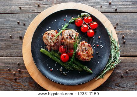 Grilled pork dish with fresh vegetable spices. Food photographyof grilled pork medallions with herbs and spices. Tasty cook meat with  vegetables on dark wooden background.