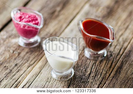 several sauces  of European cuisine. Several sauces : mayonnaise, ketchup, horseradish.  Top view on european cuisine  food on wooden background.
