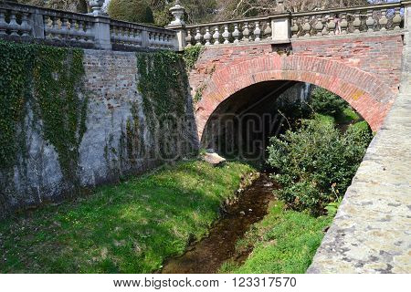 stream running beneath the bridge decorated with statues