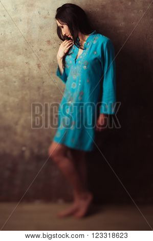 Upset indian girl in blue dress standing against stone background. Offended upset indian girl against wall. Disappointed east girl in blue dress.