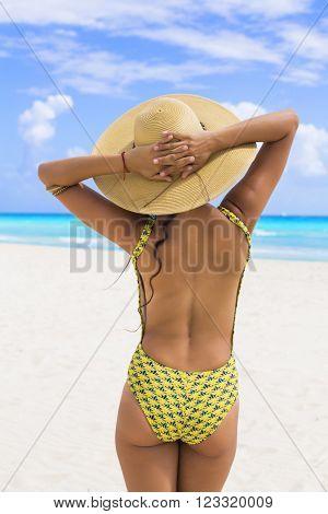 Woman in the beach wearing a hat in Playa del Carmen, Mexico.