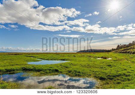 Clouds reflecting in pooling water in green fields near coastline in Grange-over-sands in Cumbria, England.
