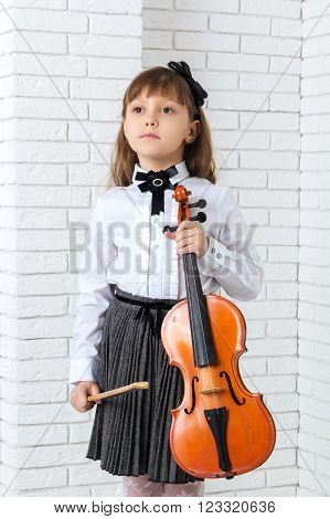 Little girl standing and holding fiddle looking away