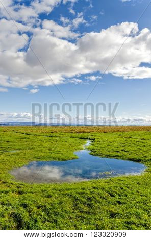 Clouds in blue skies over green fields in English countryside along coastline at Grange-over-sands in Cumbria, England.