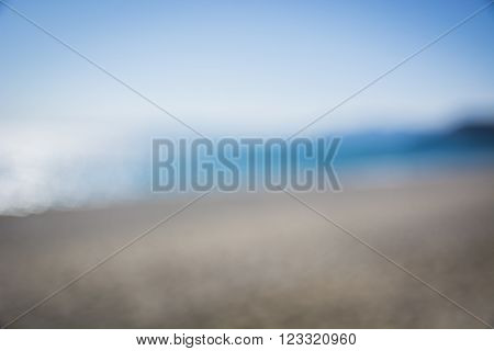 Blurred view on seashore or beach in daylight, with sea or ocean in the back