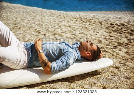 Stylish handsome young man laying on surfboard on beach in sunlight, resting with eyes closed, waiting for the waves