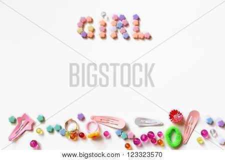 Little girl accessories lifestyle set on  white background.  Many little girl accessories scattered on blank white paper - beads, hair clips, rings. There are the inscription Girl on the top of image