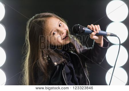 Little Girl Singing In Front Of Stage Lights