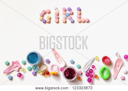 Little girl accessories lifestyle set on  white background.  Many little girl accessories scattered on blank paper - beads, hair clips, eyeshadow. The inscription Girl is on the top of image